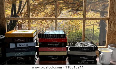 Stacks of books set on window with two coffee cups and autumn view with trees.