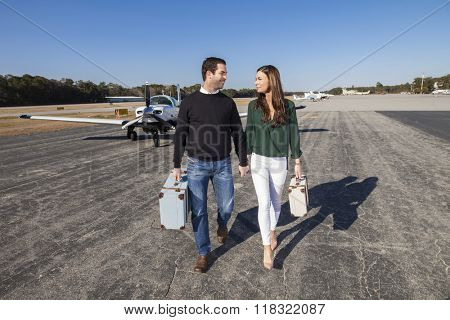 Trendy young couple walking from private plane with baggage