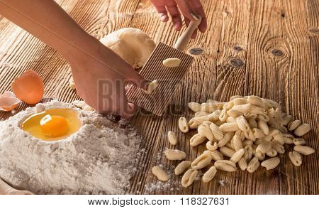 Homemade pasta rigate with egg, flour on a wood table, close-up.