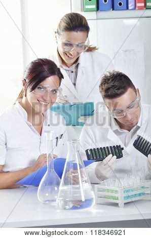 Attractive Young Phd Students Scientists  Observing The Blue, Yellow And Green Indicator Color Shift