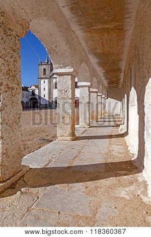 The arcades of the pilgrim lodgings in the Baroque Sanctuary of Nossa Senhora do Cabo, aka Nossa Senhora da Pedra Mua in Espichel Cape and the church at the back. Sesimbra, Portugal