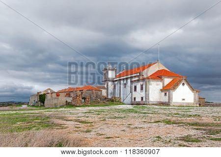 Back of the baroque church in the Sanctuary of Nossa Senhora do Cabo, aka Nossa Senhora da Pedra Mua, with ruins. Espichel Cape. Sesimbra, Portugal