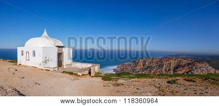 The remote Ermida da Memoria (Memory Hermitage) of the Nossa Senhora do Cabo Sanctuary, built on the edge of a cliff on Espichel Cape, with the Atlantic Ocean in background. Sesimbra, Portugal. poster