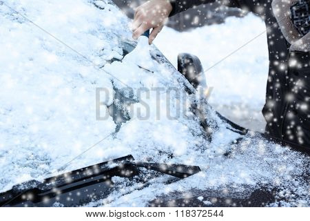 Winter driving, scraping snow from a windshield