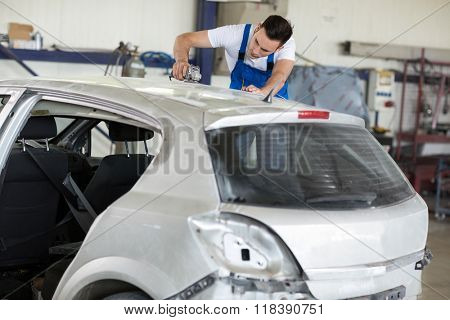Car painter polishes scratches on car in service