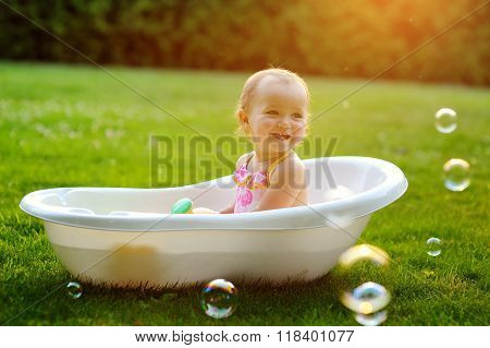 Little Girl Playing In The Bath On Grass