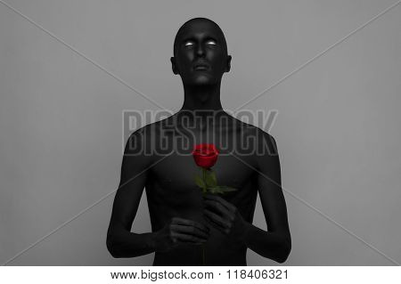 Gothic And Halloween Theme: A Man With Black Skin Holding A Red Rose, Black Death Isolated On A Gray