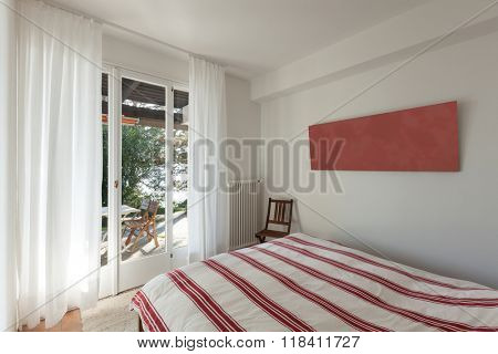 Interior of house, double bed with bedspread striped