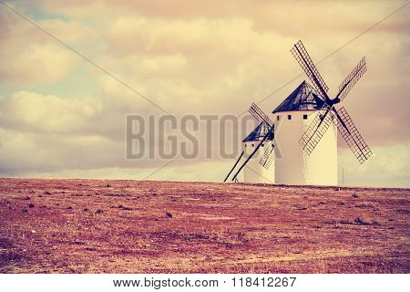 a view of some traditional white windmills in Campo de Criptana, Spain, with a filter effect and a slight vignette added