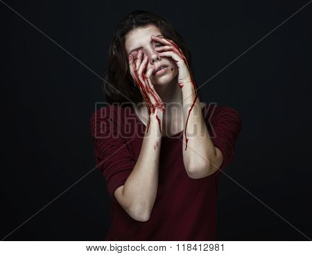 Scary Girl And Halloween Theme: Portrait Of A Crazy Girl With A Bloody Hand Covers The Face In Studi