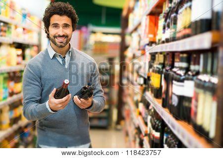 Man choosing a wine bottle in a supermarket