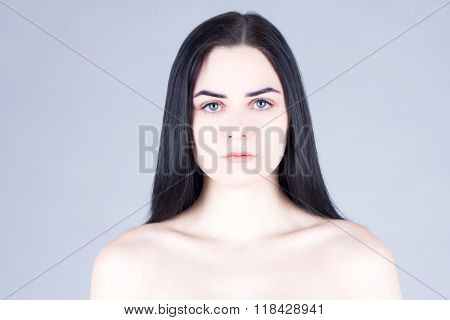 Smooth face of a woman with dark hair gray eyes and fair skin