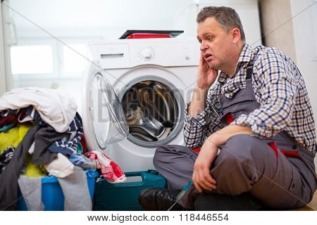 Handsome Repairman Repairing Washer In Kitchen, Sitting Next To Dirty Laundry