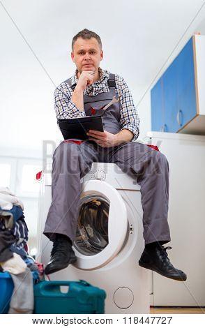 Repairman is repairing a washing machine on the white background. Entering malfunction sitting on wa