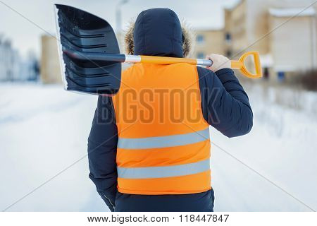 Man with snow shovel near building in winter