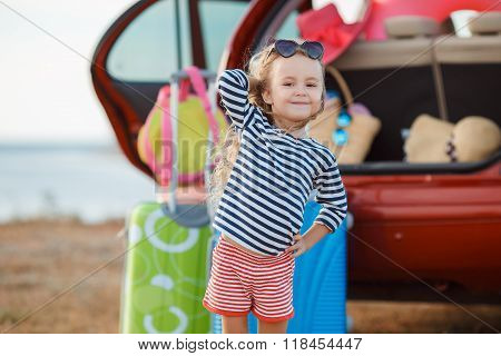 A little girl,a brunette with long curly hair,dressed in a striped sailor shirt and shorts with red stripes ,in dark sun glasses,embarks on a journey to the sea,stands near the red car loaded things,suitcases and bags poster