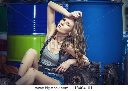 Young Sexy Woman Model In The Role Of Mechanic On The Background Of The Petrol Drums