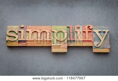simplify word in letterpress wood type printing blocks stained by color inks against slate stone