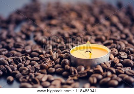 Coffee beans on a black background with candle. Raw coffee beans and fire from candle. Grained