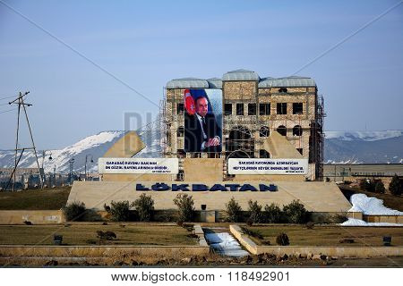 Unfinished building in Lokbatan, Azerbaijan, with large picture of Heydar Aliyev