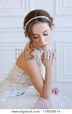 Bridal fashion. Tender young woman with brown hair and pearl headpiece wearing white gownd and light pink makeup. poster