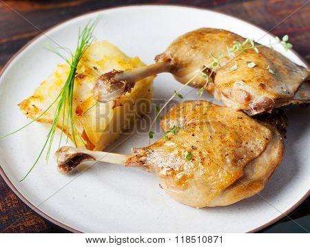 Duck legs confit with potato gratin and mushroom sauce Restaurant serving
