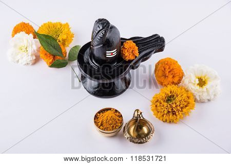 Shiva Linga made up of black stone decorated with flowers & bael leaf known as Aegle marmelos, over