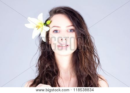 Woman with curly hair and big blue eyes. Woman with a flower in her hair.