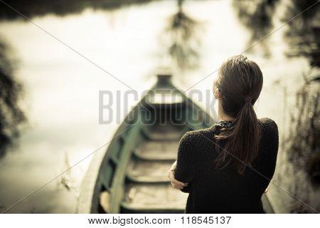 Girl at the old fishing boat looking to the lake.Melancholia sadness sorrow concept