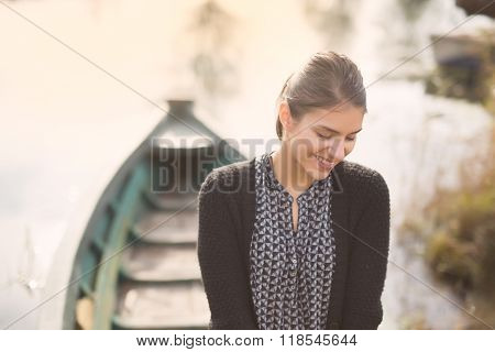 Young beautiful charming woman at the old fishing boat smiling.Honest reaction on male complimenting
