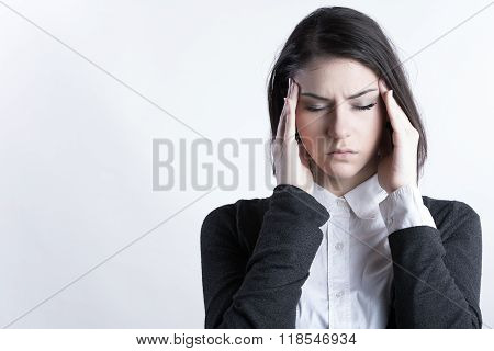 Young woman holding her head.Migraine and headache problem.Overworked,stressed woman.Menstrual and period pain.Intensive lifestyle and fast life. poster