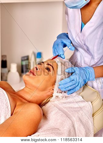 Woman middle-aged in spa salon with beautician. Female giving anti-aging injections.