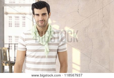 Young casual caucasian man at vintage summer Paris home. Bristly, smiling, looking at camera, standing. Copyspace.