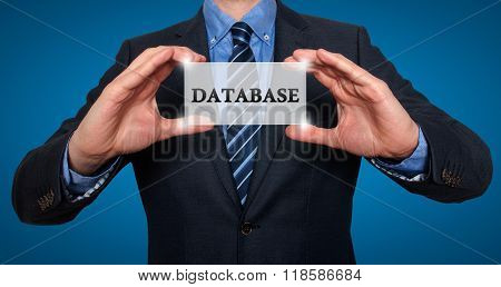 Businessman Holds White Card With Database Sign, Blue - Stock Photo