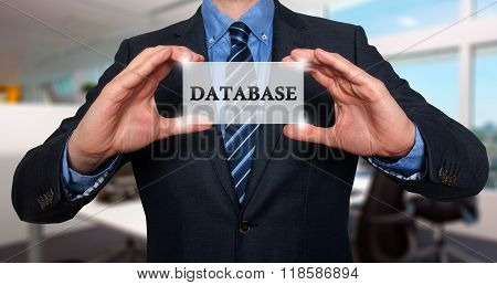 Businessman Holds White Card With Database Sign, Office - Stock Photo
