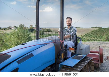 Young Farmer Toasts On A Crawler Tractor In His Vineyard