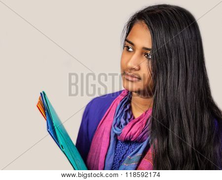 Education portrait of an pretty india woman holding notebooks on bright background . She is looking away in half-profile