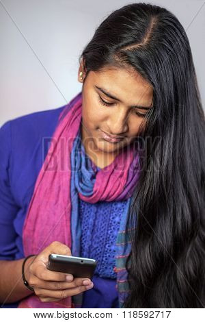 Young pretty india woman looking at her smart-phone, vertical