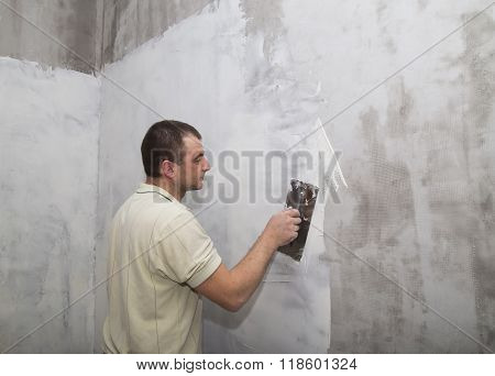 Man worker applying first layer of putty with trowel
