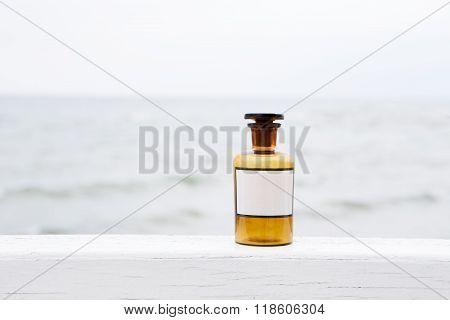 Vintage Medicine Bottle On Sea Background