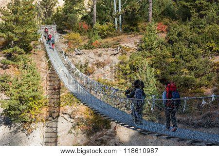 Trekkers crossing a suspension bridge.