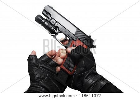 Hands in gloves reloading gun .