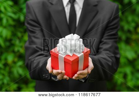 Gift And Business Theme: A Man In A Black Suit Holding A Gift In A Red Box With A White Ribbon On A