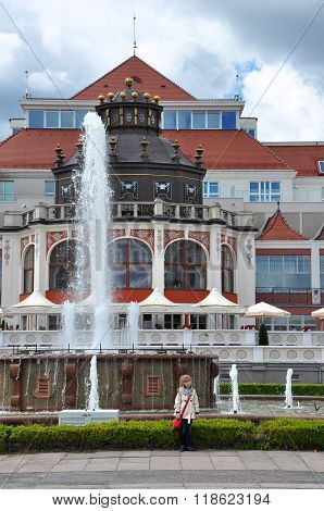 SOPOT POLAND - JUNE 23: Little girl posing with Art Noveau style Health Spa House on June 23 2015 in Sopot Poland