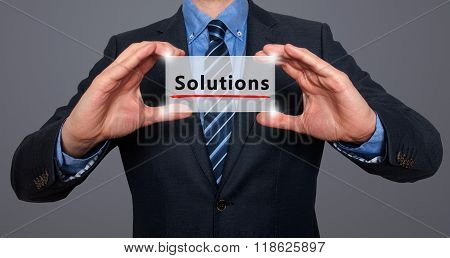 Businessman Holding White Card With Solutions Sign, Grey - Stock Photo