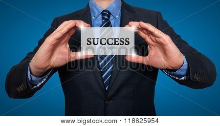 Businessman Holding White Card With Success Sign, Blue - Stock Photo