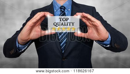 Top Quality With Five Stars - Businessman With Sign - Grey - Stock Photo