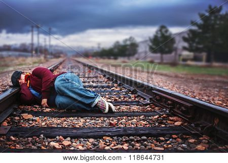 a possible homeless person or bum sleeping on railroad tracks with a storm approaching in the background