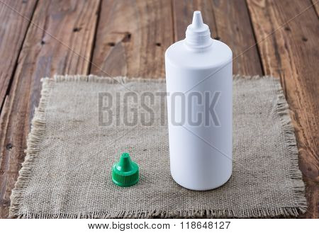 White Plastic Bottle Mock Up On Wood Background. Liquid Lens