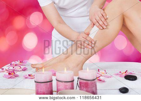 Beautician Waxing Woman's Leg In Beauty Salon